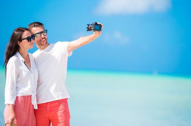 Glückliches paar, das ein selfie foto auf weißem strand macht.