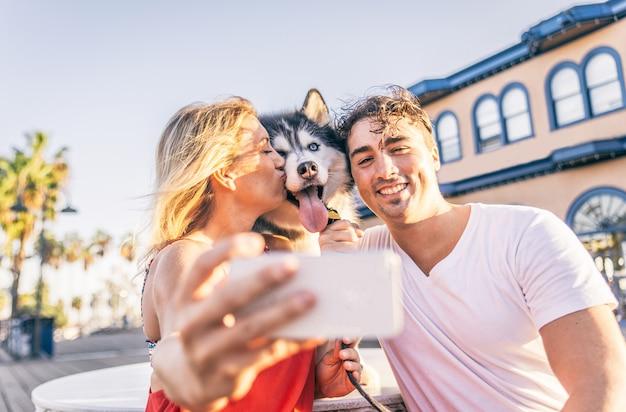 Glückliches paar, das ein selfie mit ihrem husky macht - frau, die handy hält und ein lustiges foto mit seiner familie macht