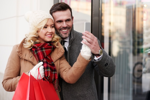 Glückliches paar, das ein selfie über einkaufen nimmt