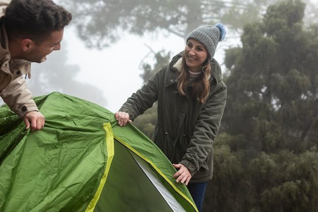 Glückliches paar, das ein zelt in der natur aufbaut