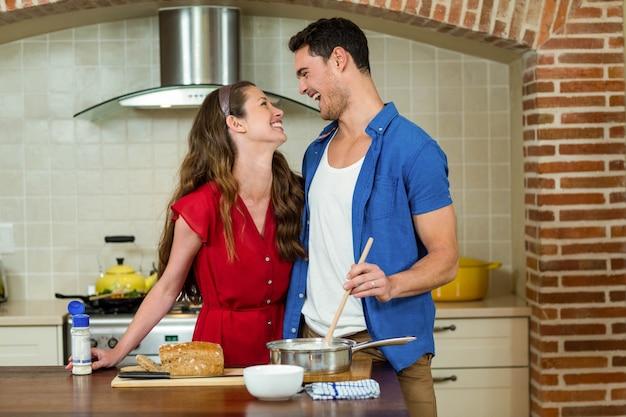 Glückliches paar, das einander betrachtet und beim zubereiten der lebensmittelküche lacht