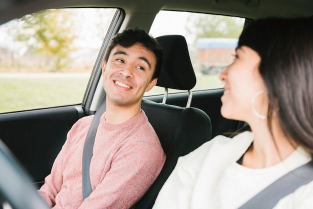 Glückliches paar, das einander im auto betrachtet