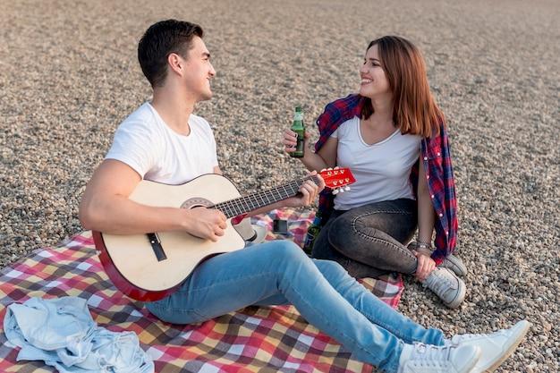 Glückliches paar, das einander in einem picknick betrachtet