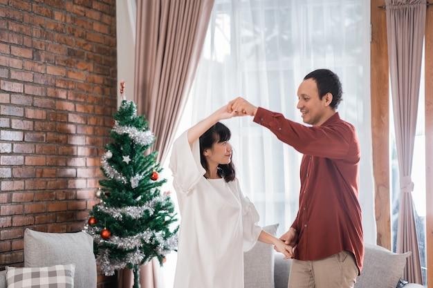 Glückliches paar, das einander tanzt während des weihnachtstages zu hause liebt