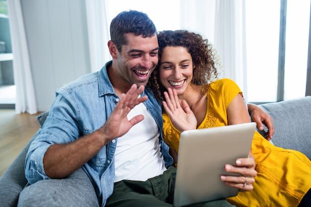 Glückliches paar, das eine digitale tablette auf sofa verwendet