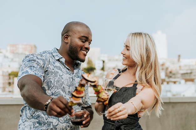 Glückliches paar, das eine grillaufsteckspindel und ein glas wein genießt