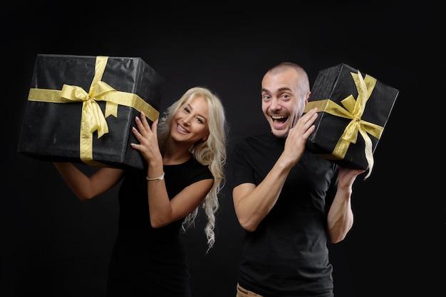 Glückliches paar, das eine schwarze geschenkbox an einer schwarzen wand hält. feiern sie die weihnachtsferien