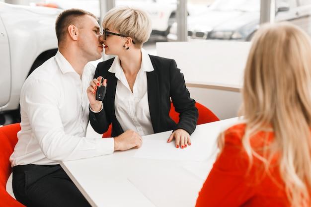Glückliches paar, das einen autoschlüssel in einem büro nach abkommen halten küsst