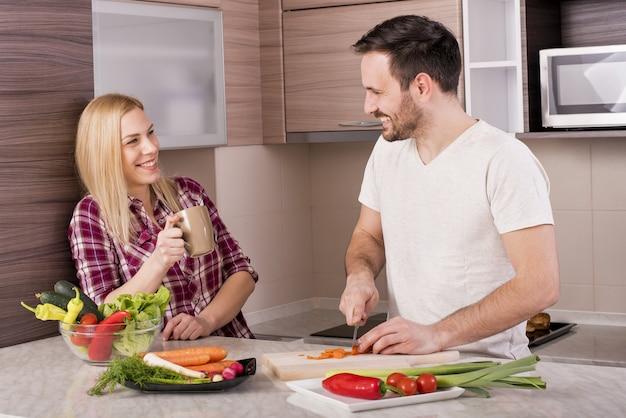 Glückliches paar, das einen frischen salat mit gemüse auf der küchentheke macht