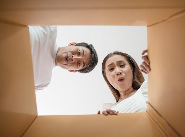 Glückliches paar, das einen kasten öffnet und nach innen zum produkt schaut