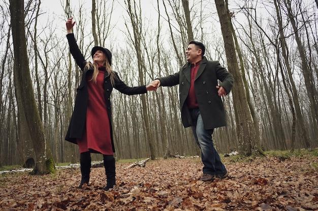Glückliches paar, das einen romantischen weg in einem wald genießt