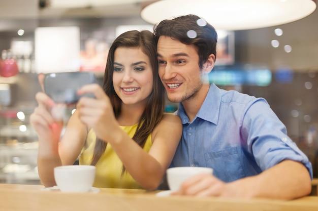 Glückliches paar, das etwas auf handy im café überprüft