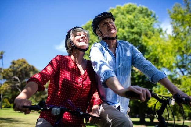 Glückliches paar, das fahrrad im park fährt