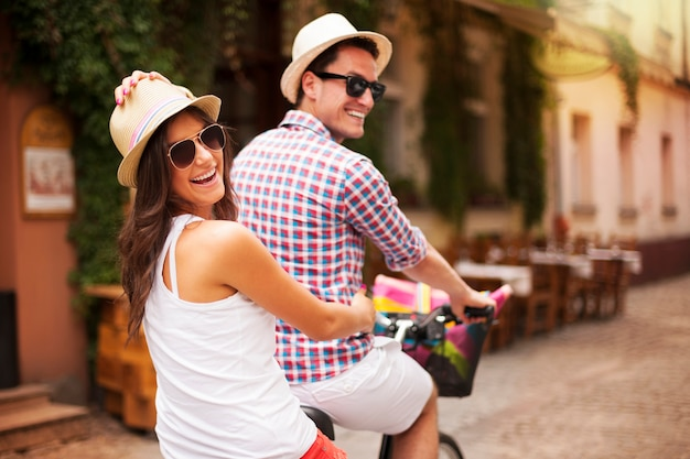 Glückliches paar, das fahrrad in der stadtstraße reitet