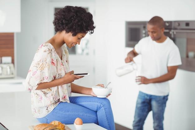 Glückliches paar, das frühstück isst und zu hause smartphone in der küche verwendet