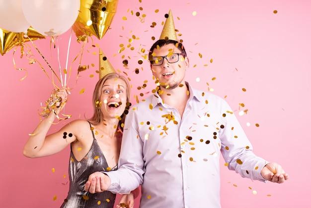Glückliches paar, das geburtstagsfeier feiert, die goldene luftballons und geschenkbox hält, goldenes konfetti werfend