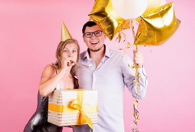 Glückliches paar, das geburtstagsfeier feiert, die goldene luftballons und geschenkbox lokalisiert auf rosa hintergrund wächst