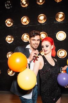 Glückliches paar, das geburtstagsfeier im nachtclub feiert