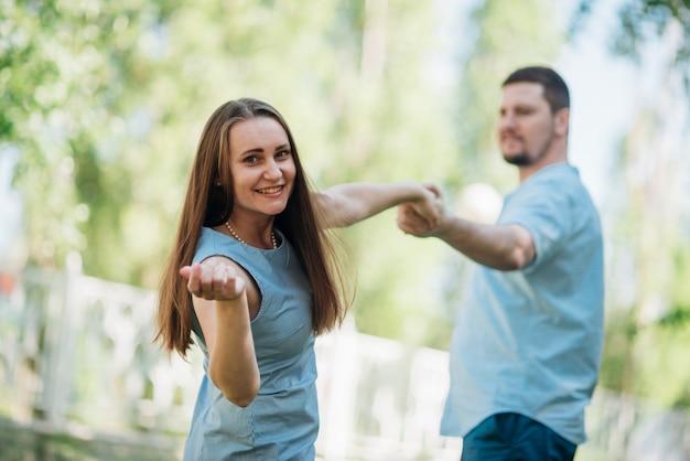 Glückliches paar, das hände im park flirtet und anhält