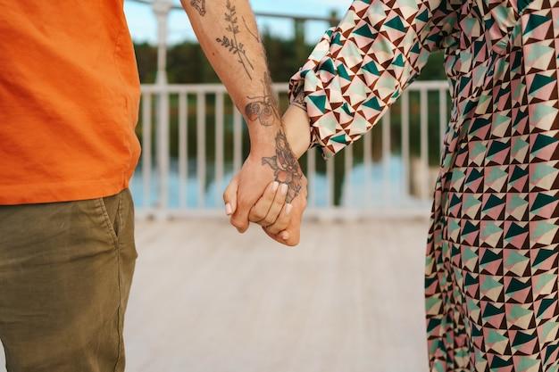 Glückliches paar, das hände in den bunten kleidern hautnah hält