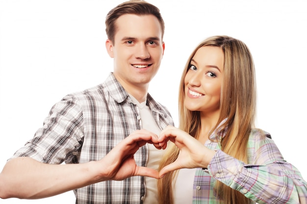 Glückliches paar, das herz mit ihren fingern zeigt