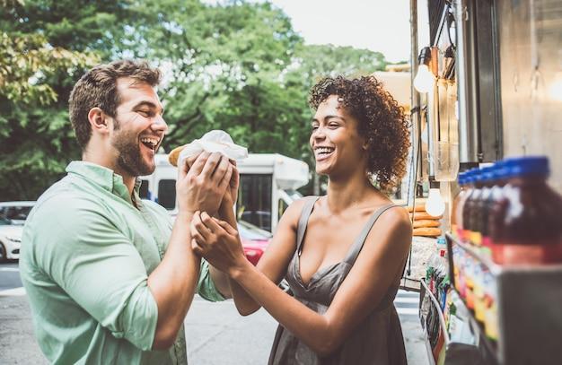 Glückliches paar, das hot dogs isst und spaß an new york hat