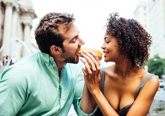 Glückliches paar, das hot dogs isst und spaß in new york city hat