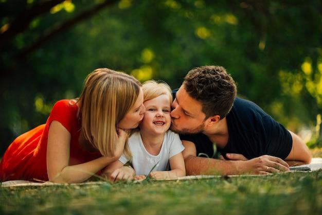 Glückliches paar, das ihr kind küsst