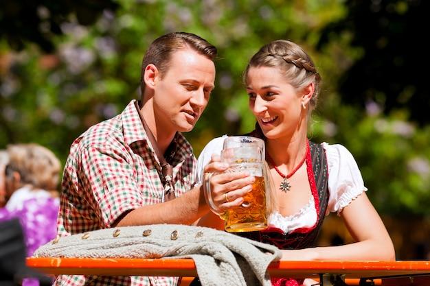 Glückliches paar, das im biergarten sitzt