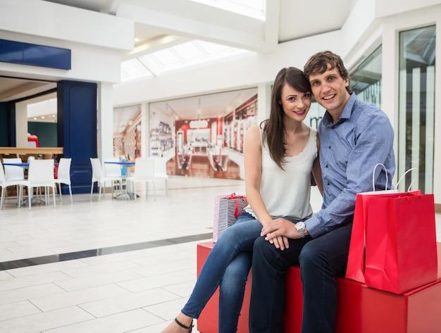 Glückliches paar, das im einkaufszentrum sitzt