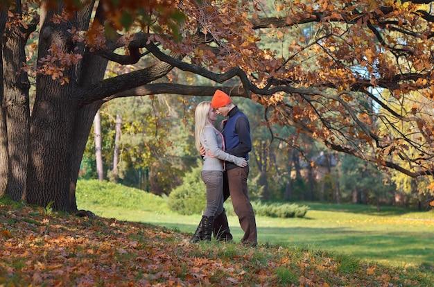 Glückliches paar, das im herbstpark bei gutem wetter ruht
