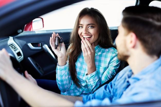 Glückliches paar, das im neuen auto sitzt und kamera betrachtet, lächelt, neue schlüssel hält, verließ.