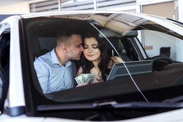 Glückliches paar, das im neuen auto sitzt und lächelt