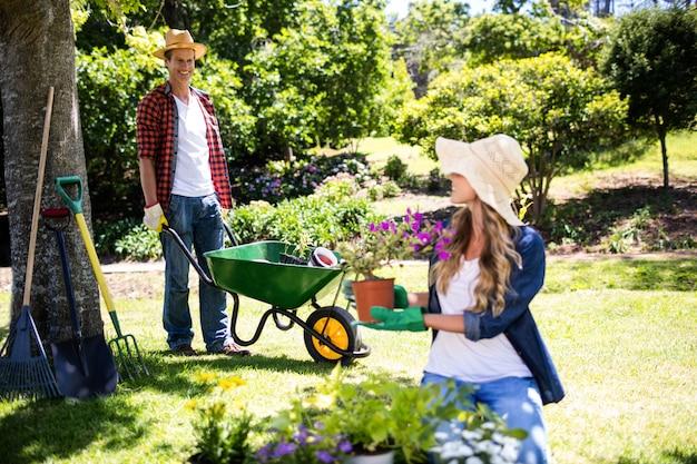 Glückliches paar, das im park im garten arbeitet