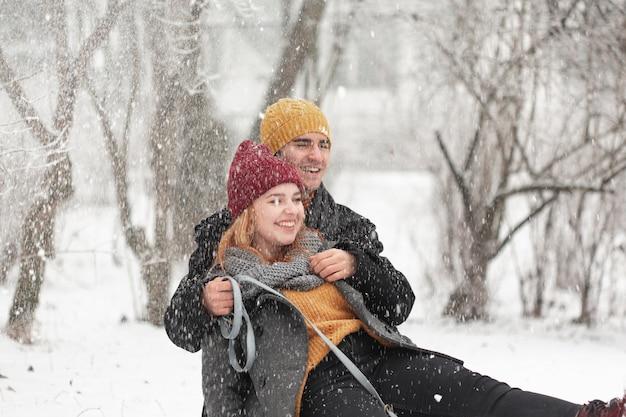 Glückliches paar, das im schnee sitzt