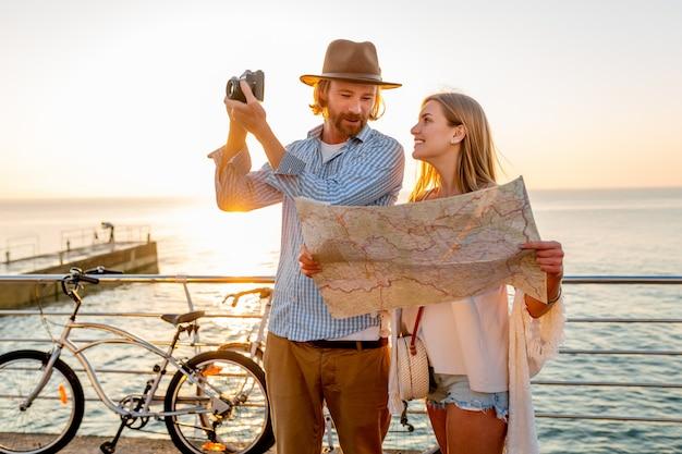 Glückliches paar, das im sommer auf fahrrädern reist, eine karte schaut und fotos vor der kamera macht