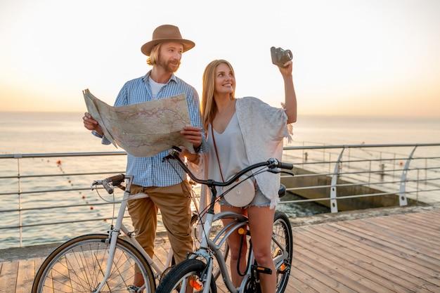 Glückliches paar, das im sommer auf fahrrädern reist, in der karte sightseeing schaut und fotos macht
