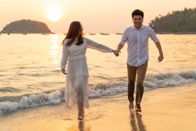 Glückliches paar, das im sommer flitterwochen auf tropischem sandstrand geht