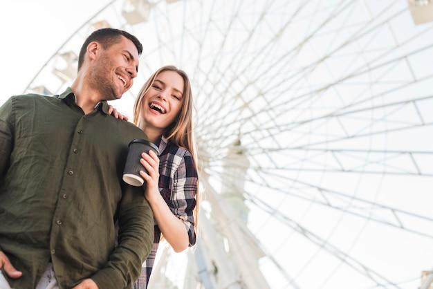 Glückliches paar, das im vergnügungspark genießt
