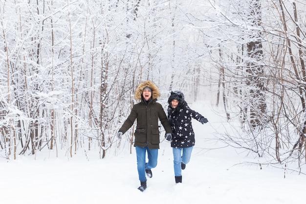 Glückliches paar, das im winter durch einen verschneiten wald geht