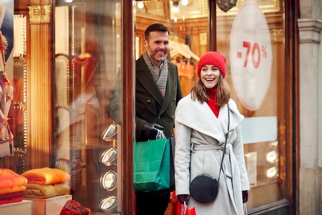 Glückliches paar, das im winterverkauf einkauft