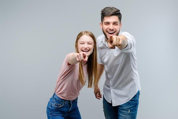 Glückliches paar, das in camera die finger lokalisiert über grauem hintergrund lacht und zeigt