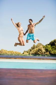 Glückliches paar, das in das pool an einem sonnigen tag springt