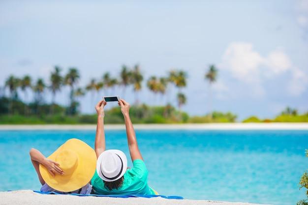 Glückliches paar, das in den flitterwochen ein foto am weißen strand macht