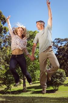 Glückliches paar, das in den park springt