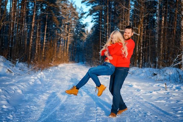 Glückliches paar, das in den schneebedeckten wald geht