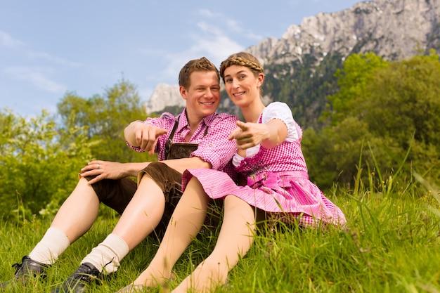 Glückliches paar, das in der alpenwiese sitzt