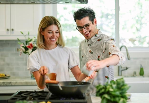Glückliches paar, das in der küche kocht