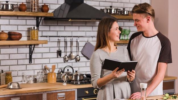 Glückliches paar, das in der küche mit notizbuch steht