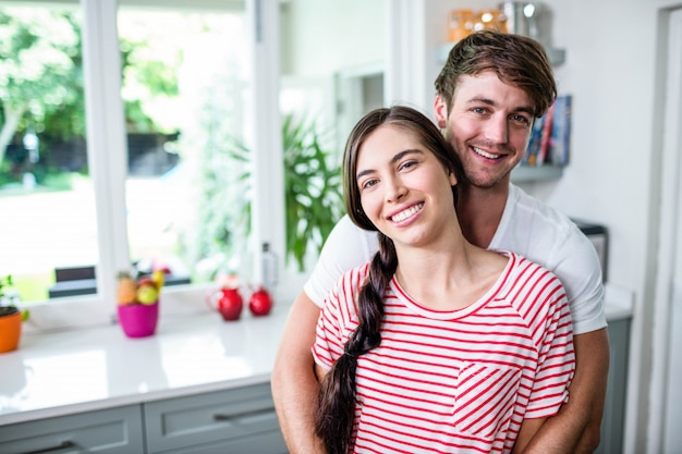 Glückliches paar, das in der küche steht und die kamera betrachtet
